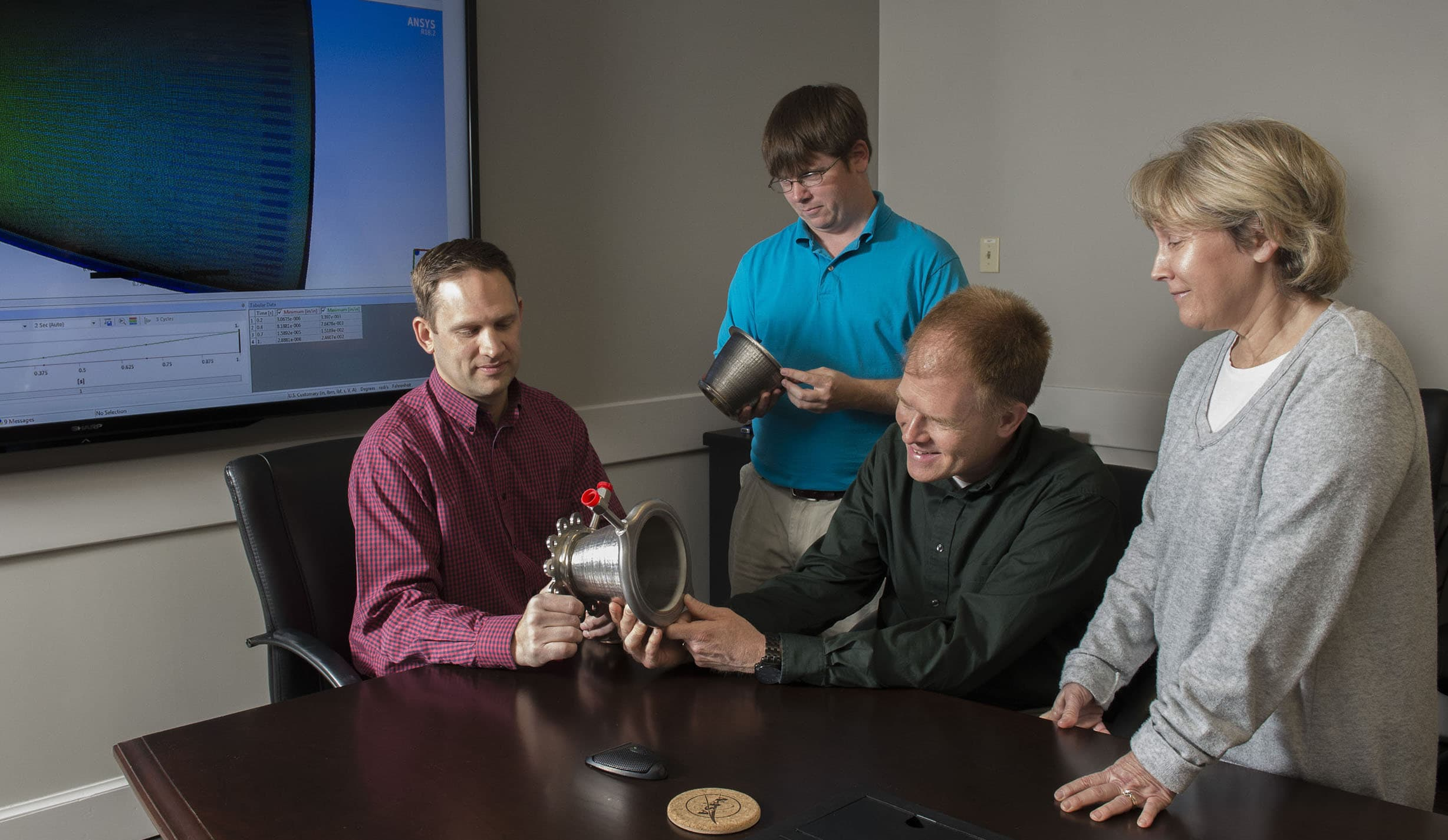 Engineers from NASA Marshall Space Flight Center's Propulsion Department examine nozzles fabricated using Laser Wire Direct Closeout